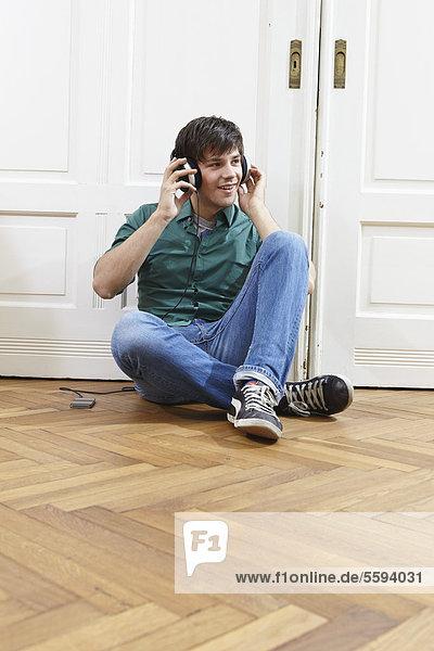 Junger Mann mit Kopfhörer,  lächelnd