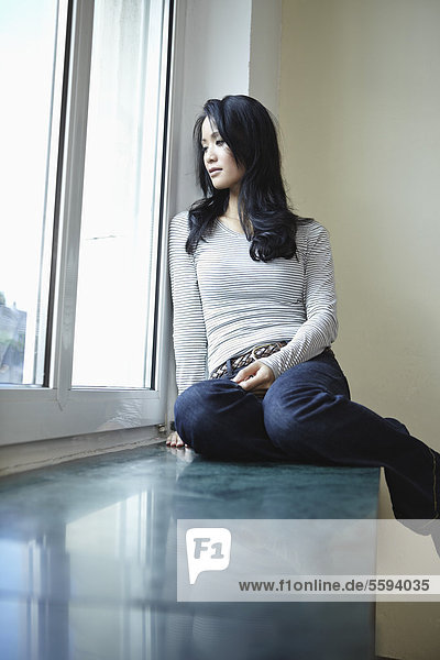 Junge Frau am Fenster sitzend