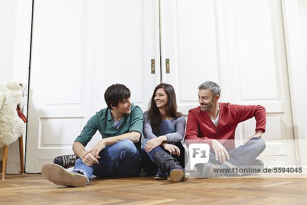 Mann und Frau sitzen neben der Tür und lächeln.