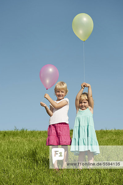 Girls standing in grass with balloons