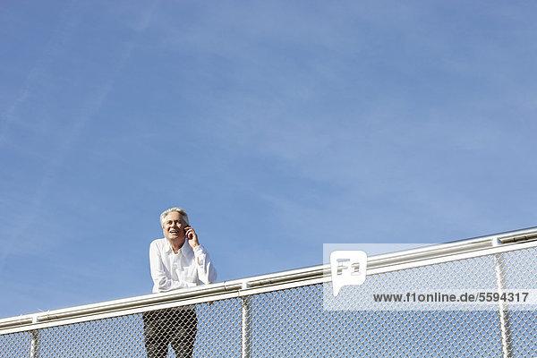 Deutschland  Bayern  München  Geschäftsmann am Telefon  lächelnd