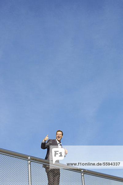 Deutschland  Bayern  München  Geschäftsmann am Geländer stehend  lächelnd