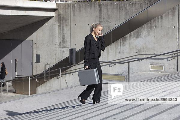 Geschäftsfrau auf der Treppe mit Aktentasche und Gespräch am Handy  lächelnd