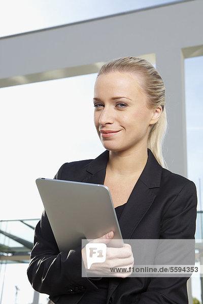 Geschäftsfrau mit digitalem Tablett  lächelnd  Portrait