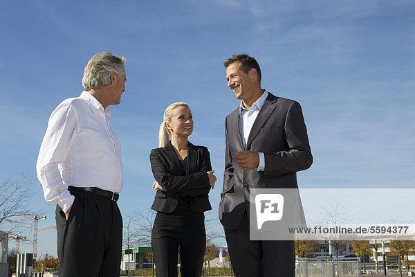 Deutschland  Bayern  München  Geschäftsleute  die gegen den Himmel stehen  lächelnd
