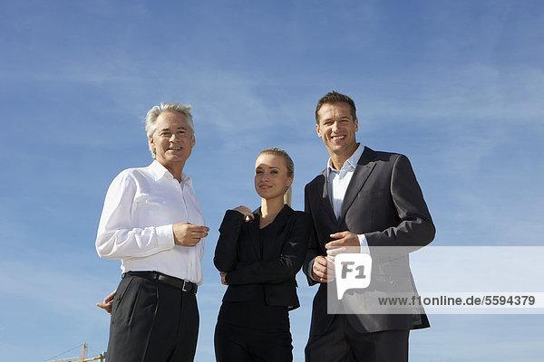 Deutschland  Bayern  München  Geschäftsleute gegen den Himmel  lächelnd  Portrait