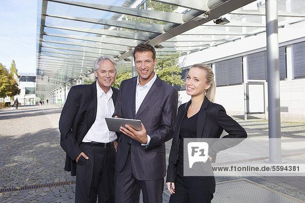 Deutschland  Bayern  München  Geschäftsleute mit digitalem Tablett  lächelnd  Portrait