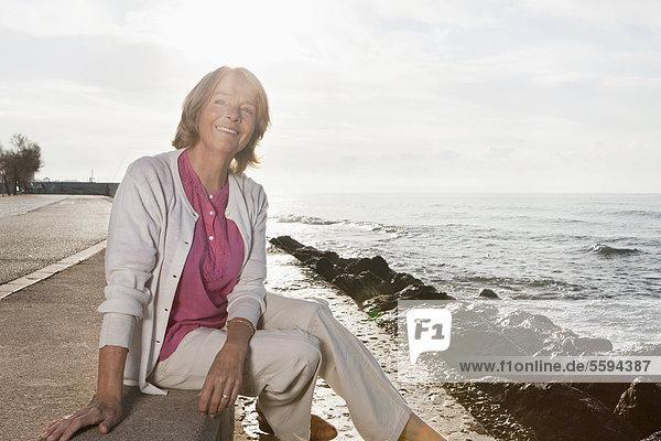 Spanien  Mallorca  Seniorin am Meer sitzend  lächelnd  Portrait