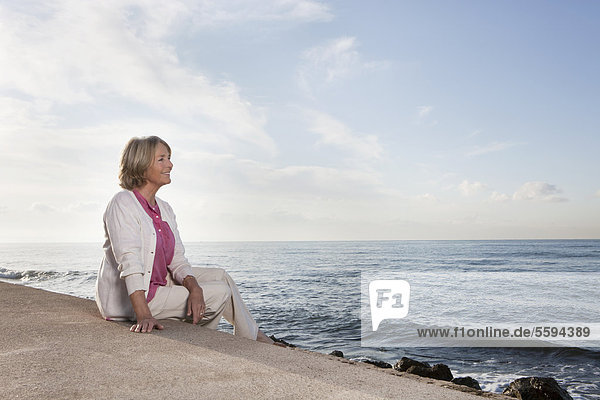 Spanien  Mallorca  Seniorin am Meer sitzend  lächelnd