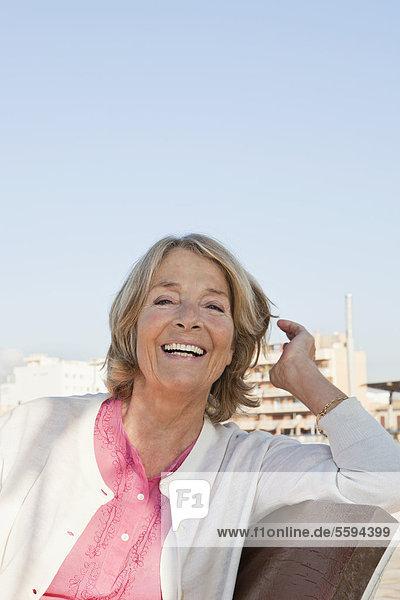 Spanien  Mallorca  Seniorin auf Bank am Meer sitzend  lächelnd  Portrait