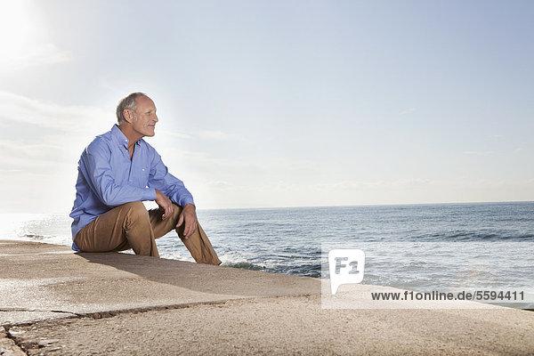 Spanien  Mallorca  Senior Mann am Meer sitzend