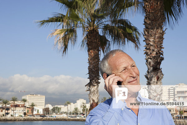 Spanien  Mallorca  Senior Mann auf dem Handy am Meer