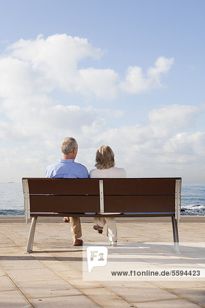 Spanien  Mallorca  Seniorenpaar auf Bank am Meer sitzend