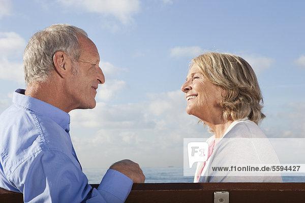 Spanien  Mallorca  Seniorenpaar auf Bank am Meer sitzend  lächelnd