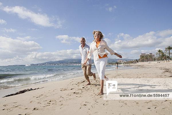 Spanien  Mallorca  Seniorenpaar am Strand entlang  lächelnd