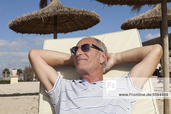 Spanien  Mallorca  Senior Mann auf Liegestuhl am Strand