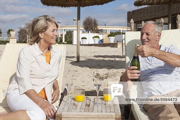 Spanien  Mallorca  Seniorenpaar mit Getränk am Strand