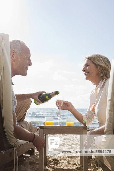 Spanien  Mallorca  Seniorenpaar trinkt Sekt am Strand  lächelt