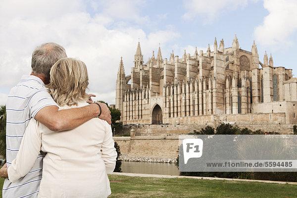 Spanien  Mallorca  Palma  Seniorenpaar lächelt mit Kathedrale Santa Maria
