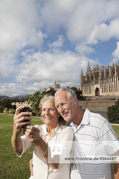 Spanien  Mallorca  Palma  Seniorenpaar lächelnd beim Fotografieren mit der Kathedrale Santa Maria  Portrait