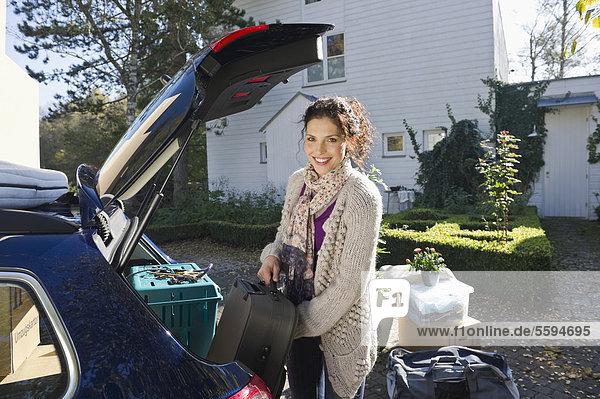 Mittlere erwachsene Frau beim Beladen des Kofferraums  lächelnd  Portrait