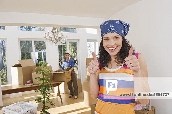 Frau gestikuliert mit Mann im Hintergrund  lächelnd  Portrait