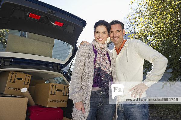 Deutschland  Bayern  Grobenzell  Paar neben dem Auto stehend  lächelnd  Portrait