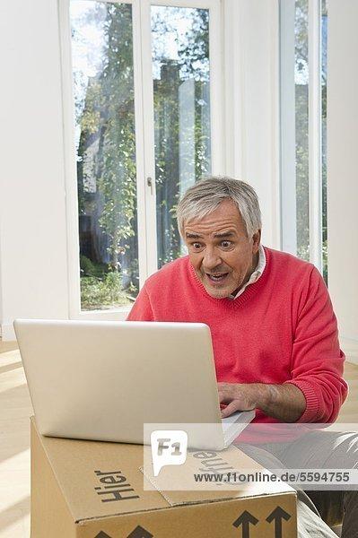 Senior Mann mit Laptop auf Pappkarton