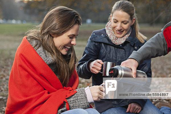 Deutschland  Berlin  Wandlitz  Freunde trinken Heißgetränk  lächeln