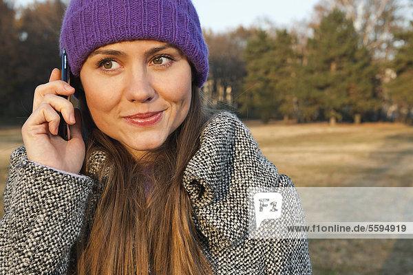 Mid adult woman using cell phone  smiling