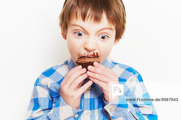 Junge  der einen Muffin verschlingt.