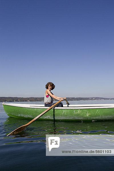Woman rowing boat in still lake