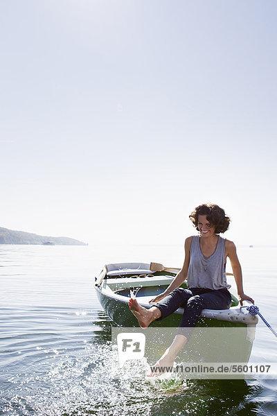 Woman dangling feet from boat in lake