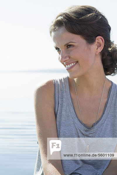 Smiling woman sitting by water