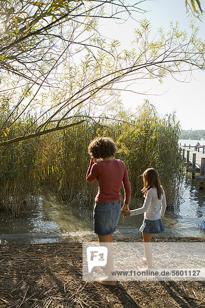 Mother and daughter walking by lake