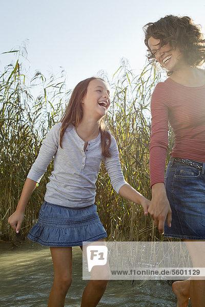 Mutter und Tochter beim Spaziergang im Teich