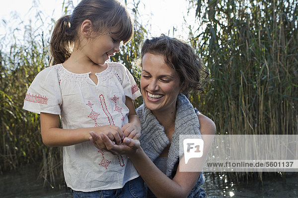 Mother and daughter talking in pond