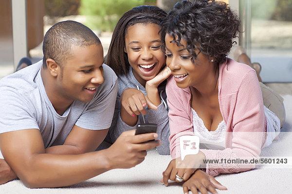 Lächelnde Familie mit dem Handy zusammen
