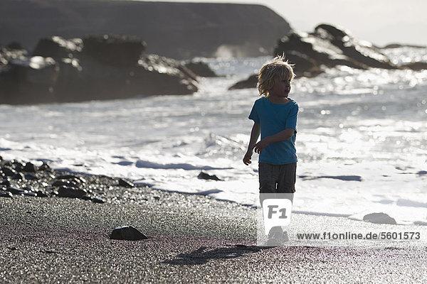 Boy walking in waves on beach