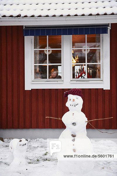 Snowmen standing outside house