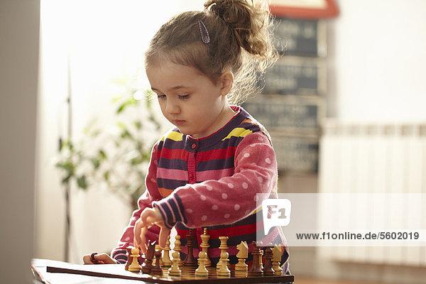 Mädchen beim Schachspielen im Haus