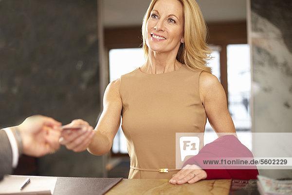 Geschäftsfrau beim Bezahlen an der Hotelrezeption
