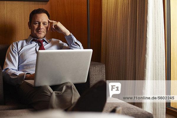 Businessman using laptop in hotel room