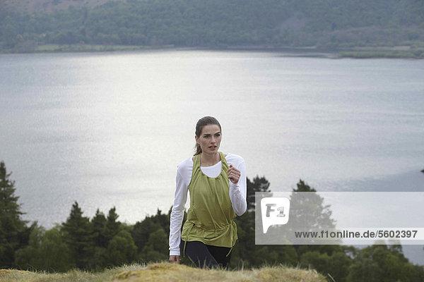 Woman climbing rural hill
