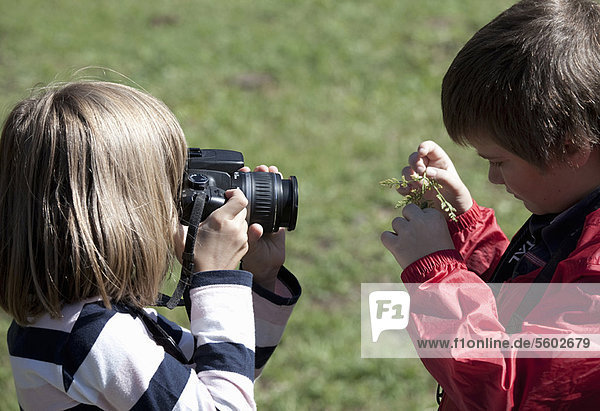 Children taking pictures outdoors
