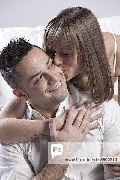 Lächelnde paar küssen auf couch