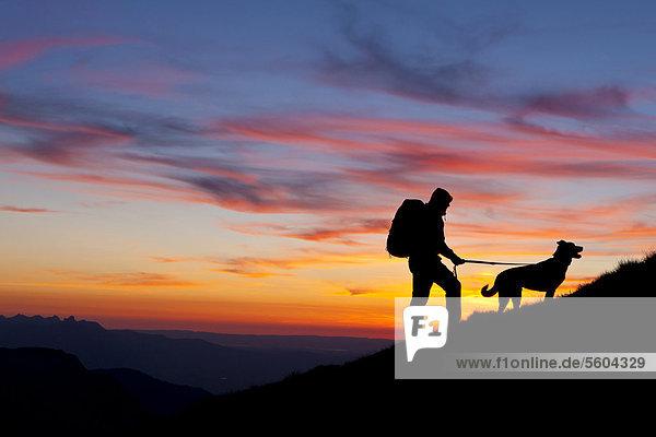 Wanderer mit Hund  Silhouetten bei Sonnenuntergang  Abendstimmung  Berner Oberland  Schweiz  Europa Wanderer mit Hund, Silhouetten bei Sonnenuntergang, Abendstimmung, Berner Oberland, Schweiz, Europa