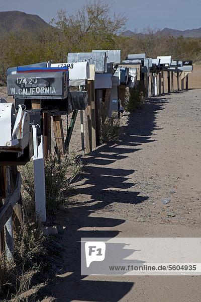 Eine lange Reihe mit Briefkästen stehen entland einer unbefestigten Straße in der Wüste westlich von Tuscon  Three Points  Arizona  USA