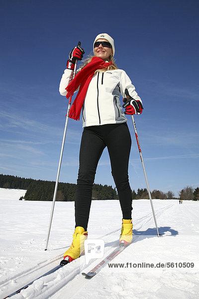 Junge Frau  etwa 25 Jahre  vor stahlblauem Himmel beim Skilanglauf  bei Masserberg  Thüringer Wald  Thüringen  Deutschland  Europa