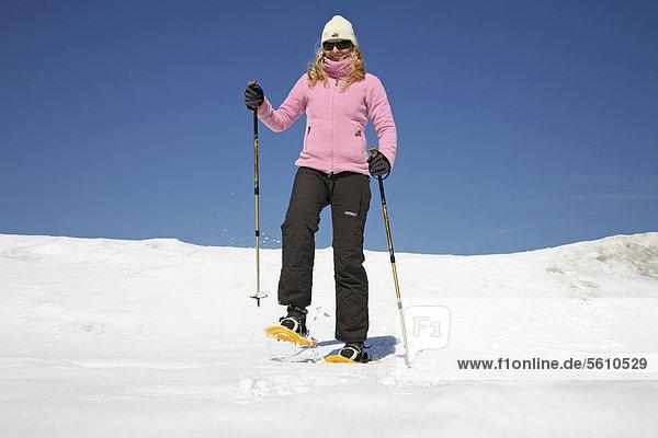 Junge Frau  etwa 25 Jahre  beim Schneeschuhfahren mit Stöcken in der Hand  vor stahlblauem Himmel  Thüringer Wald  Thüringen  Deutschland  Europa